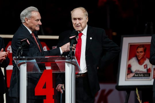 Red Kelly, right, speaks as Mickey Redmond holds the microphone during Kelly's No. 4 retirement ceremony at Little Caesars Arena in Detroit, Friday, Feb. 1, 2019.