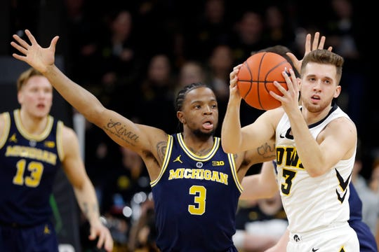 Iowa guard Jordan Bohannon grabs a loose ball in front of Michigan guard Zavier Simpson during the first half Friday, Feb. 1, 2019, in Iowa City, Iowa.