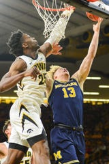 Michigan forward Ignas Brazdeikis shoots as Iowa forward Tyler Cook defends during the first half Feb. 1, 2019 in Iowa City, Iowa.