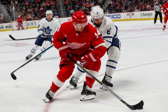 Gustav Nyquist is defended by Leafs defenseman Jake Muzzin during the first period at Little Caesars Arena on Friday.