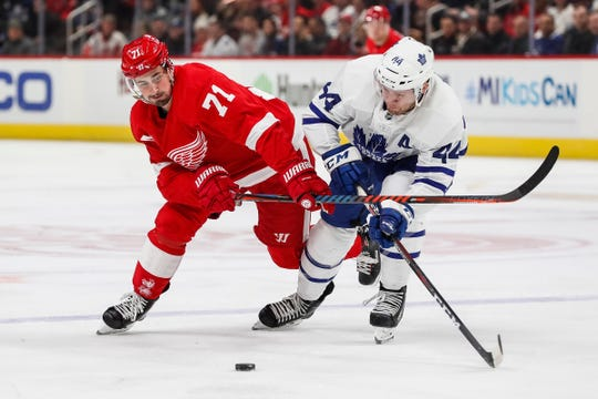 Dylan Larkin and Leafs defenseman Morgan Rielly battle for the puck in the first period Friday at LCA.