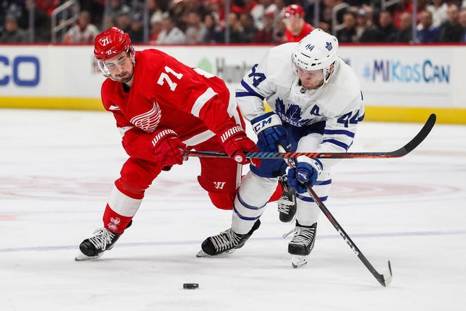 Red Wings forward Dylan Larkin and Maple Leafs defenseman Morgan Rielly battle for the puck during the first period at Little Caesars Arena in Detroit, Friday, Feb. 1, 2019.