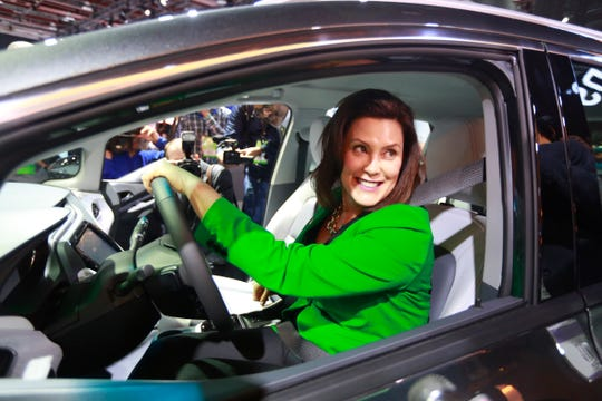 Michigan Gov. Gretchen Whitmer takes a look at the Chevrolet Bolt with General Motors Vice President Gerald Johnson (not shown) as she tours the 2019 North American International Auto Show held at Cobo Center in downtown Detroit on Tuesday, Jan. 15, 2019