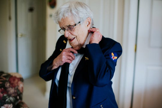 FILE -- Mildred (Jane) Doyle, a member of the Women Airforce Service Pilots during World War II,  fixes her tie while putting on her dress uniform at her Grand Rapids, Michigan, home on Nov. 7, 2017.  The WASP dress uniform consists of a Santiago Blue jacket, slacks or skirt, a white shirt, black tie, beret, and black shoes.