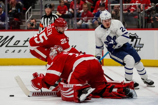 Red Wings goaltender Jimmy Howard (35) and defenseman Mike Green (25) defend the goal from Maple Leafs forward Kasperi Kapanen (24) during the second period at the Little Caesars Arena in Detroit, Friday, Feb. 1, 2019.
