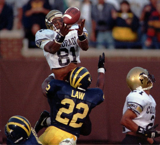 Colorado's Michael Westbrook reaches over Michigan's Ty Law to make the winning catch with no time left in Colorado's 27-26 win in Ann Arbor, Sept. 24, 1994. The 64-yard Hail Mary pass from QB Kordell Stewart was tipped by another player before Westbrook made his catch.