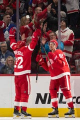Detroit center Andreas Athanasiou, left, and defenseman Danny DeKeyser celebrate DeKeyser's game winning goal in overtime.           Photos are of the Detroit Red Wings vs. the Toronto Maple Leafs, at Little Caesars Arena, in Detroit, February 1, 2019.  (David Guralnick / The Detroit News)