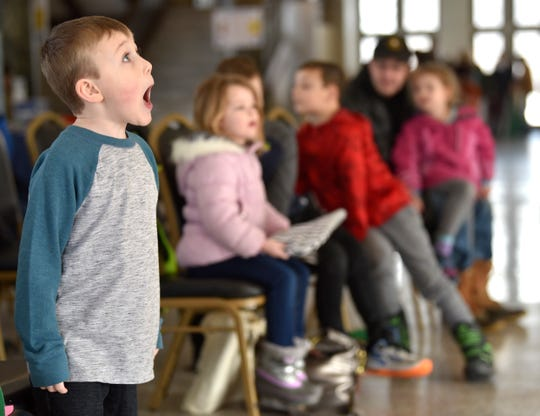 Nathan Ford, 5, watches his Uncle John Anderson (not pictured), 'Magic John the Magician,' as he performs magic tricks, Saturday.