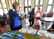 Michigan Sea Grant educator Mary Bohling, left, of Allen Park, talks with Brooklyn Thomas, 9, of Warren, as she educates people about how to keep marshes healthy and keep invasive species out of marshes like the Sea Lamprey in the jar.