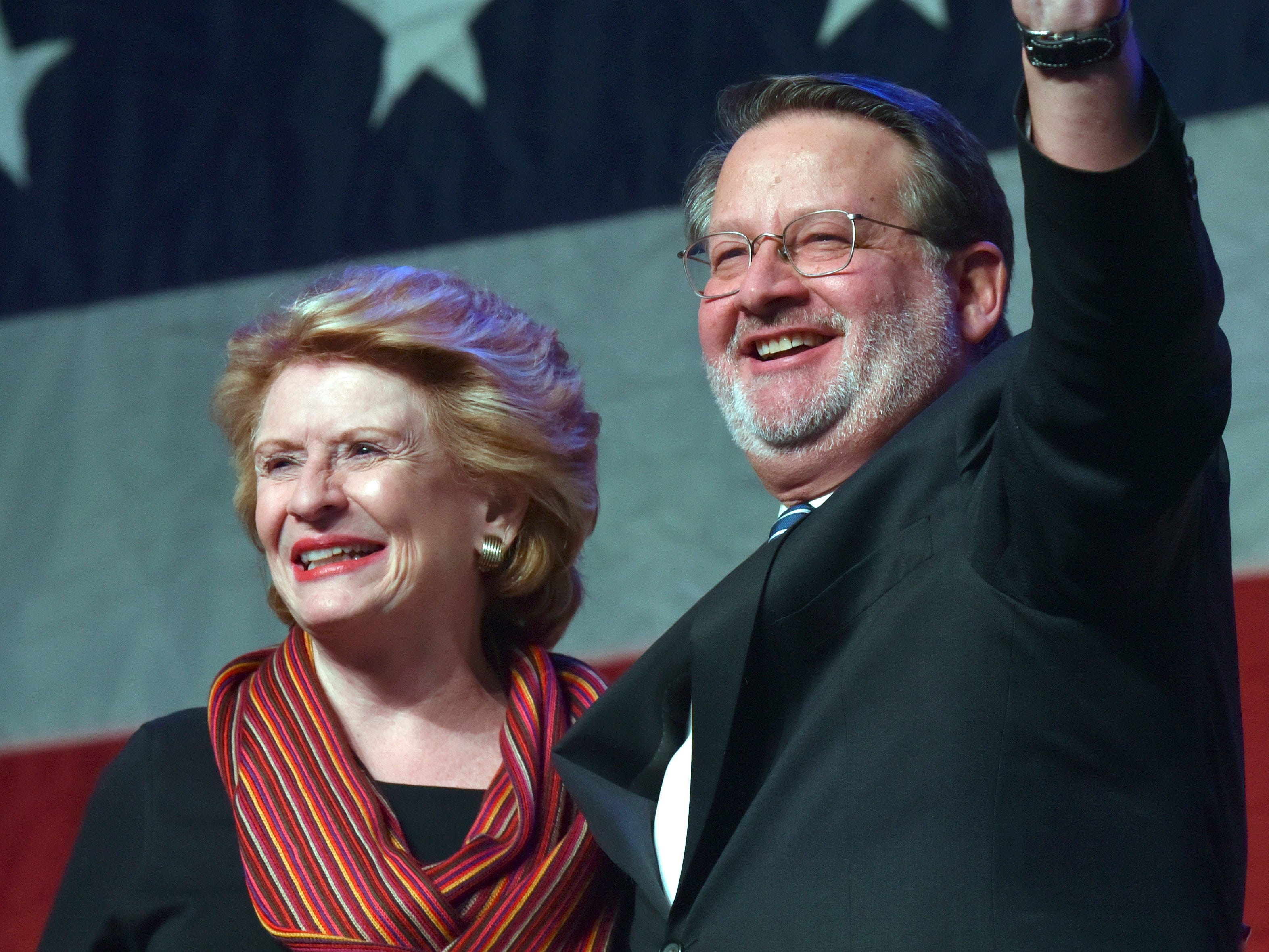 U.S. Senators Debbie Stabenow, left, and Gary Peters briefly stand together on stage after she introduces him after her speech and before his.