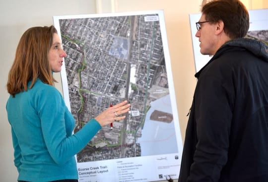 Ecorse resident Kelly Rose, left, talks to David McMillin, of Allen Park, about bike trails, including, the Ecorse Creek Trail: Conceptual Layout map.