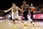Michigan guard Charles Matthews drives past Iowa forward Nicholas Baer, left, during the first half.