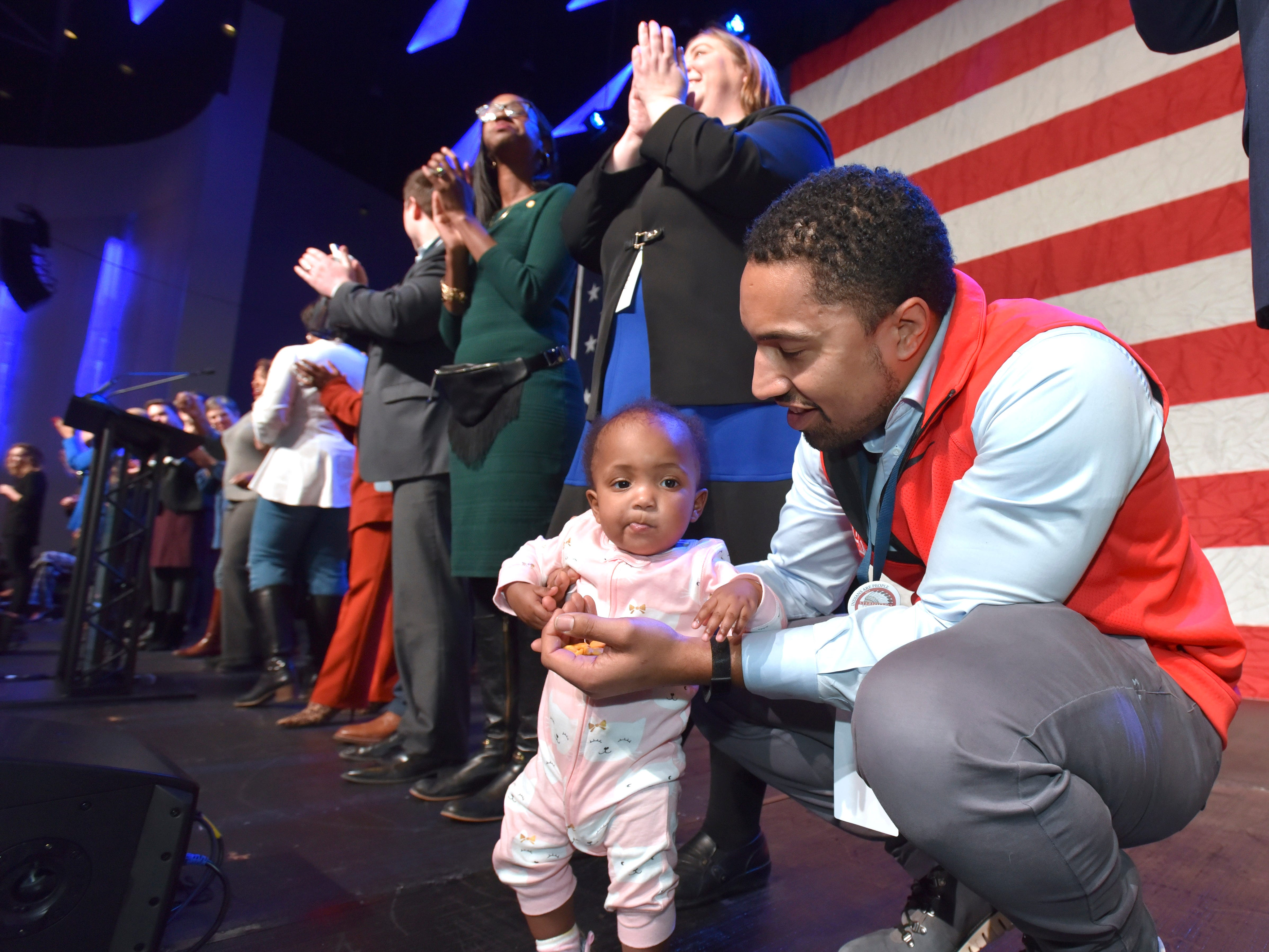 State Senator Adam Hollier tends to his one-year-old daughter, Lillian Hollier, as state senators and representatives are recognized on stage.