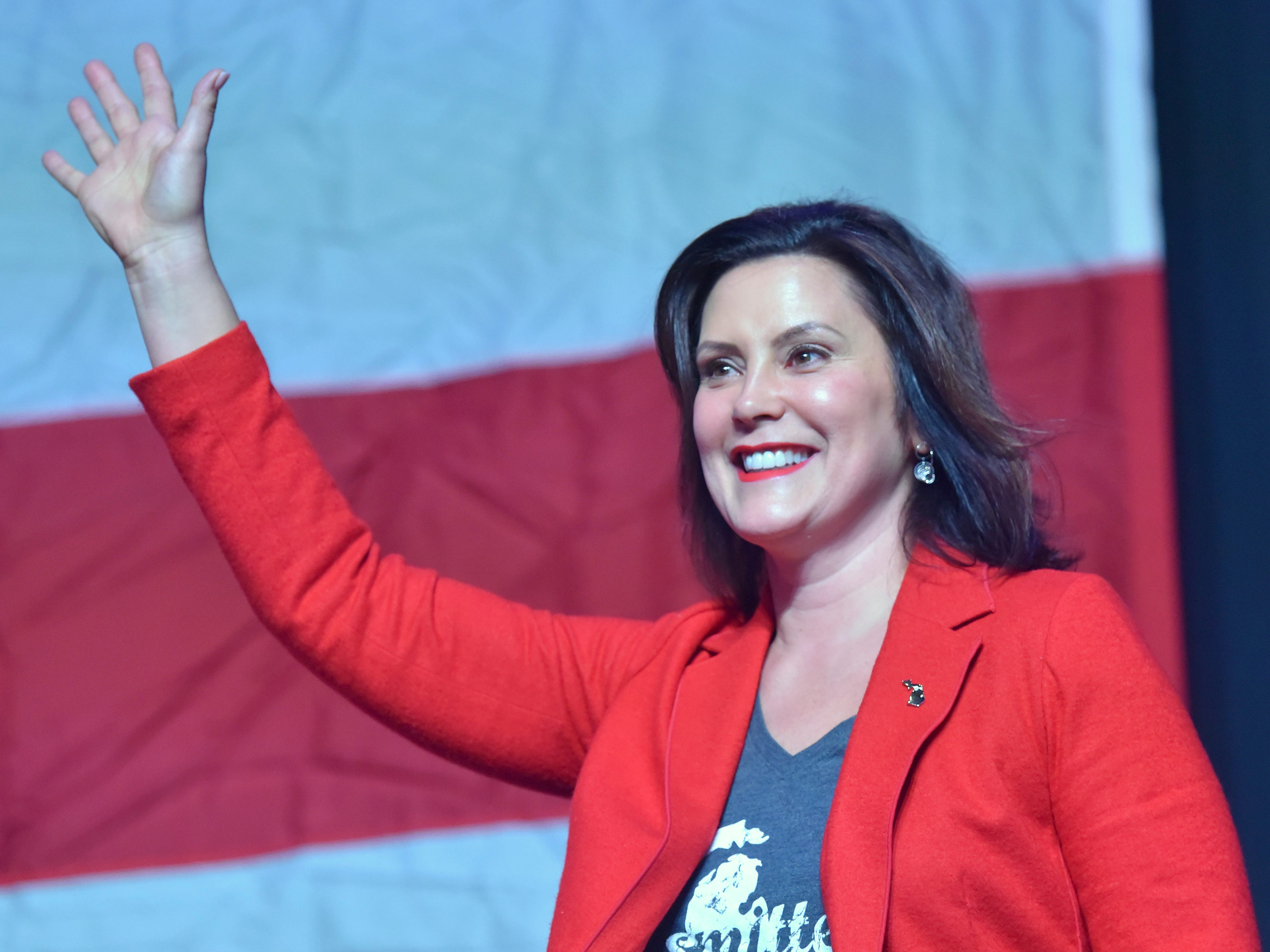 Governor Gretchen Whitmer waves at supporters as she takes the stage to speak.