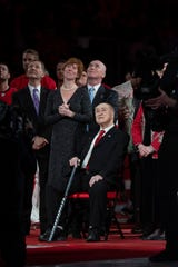 Red Kelly, seated, and his family, watch as a banner with his No. 4 is raised to the rafters at LCA in February.