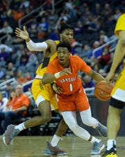 University of Evansville's Marty Hill (1) dribbles around Valparaiso's Bakari Evelyn (4) during the second half at Ford Center in Evansville, Ind., Saturday, Feb. 2, 2019. The Purple Aces snapped back from a four-game losing streak by defeating the Crusaders, 64-53.
