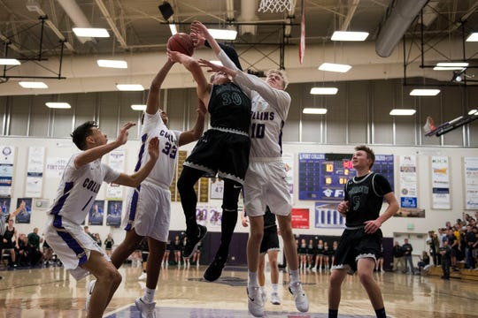 Fossil Ridge High School senior Zach Crane (30) is defended by Fort Collins High School sophomore Jackson Brigge (10) and Emeri Palacio (33) on Friday, Feb. 1, 2019, at Fort Collins High School in Fort Collins, Colo.