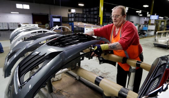 This Wednesday, Nov. 28, 2018 photo shows Clifford Goff, a bezel assembler, transferring a front end of a General Motors Chevrolet Cruze during assembly at Jamestown Industries, in Youngstown, Ohio. The sting from a major restructuring coming this year at General Motors is sure to be felt far beyond the five North American factories that are slated to close in the coming months. Thousands of jobs at auto parts suppliers and other industry-related positions are at stake as well.