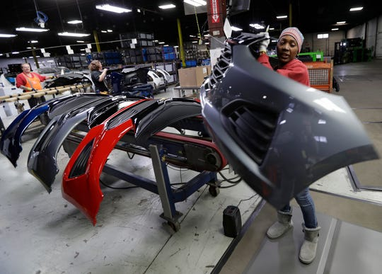 This Wednesday, Nov. 28, 2018 photo shows Mari Keels transferring a front end of a General Motors Chevrolet Cruze during assembly at Jamestown Industries, in Youngstown, Ohio. Jamestown Industries, which supplies front and rear bumper covers for the Cruze, hopes its efforts to secure new business will allow its Youngstown plant to keep going. But the plant is down from three shifts to one and GM is still its biggest customer.