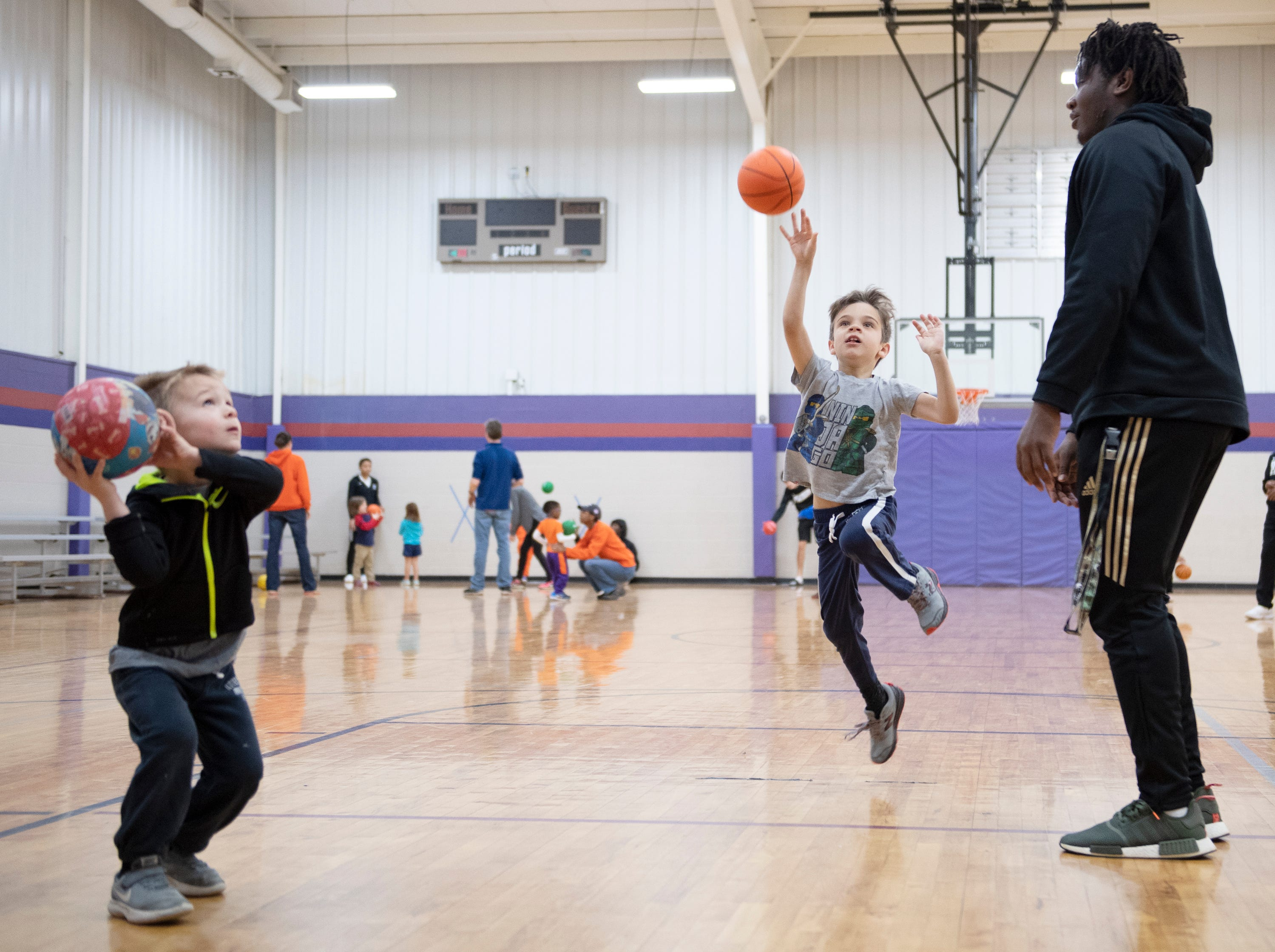 From right, D.W. Daniel High School's Jared Kirksey works with Filip Ziolkowski, 6, and Benjamin Touchberry, 4, during the Smart Start Basketball program at Central-Clemson Recreational Center Saturday, Feb. 2, 2019.