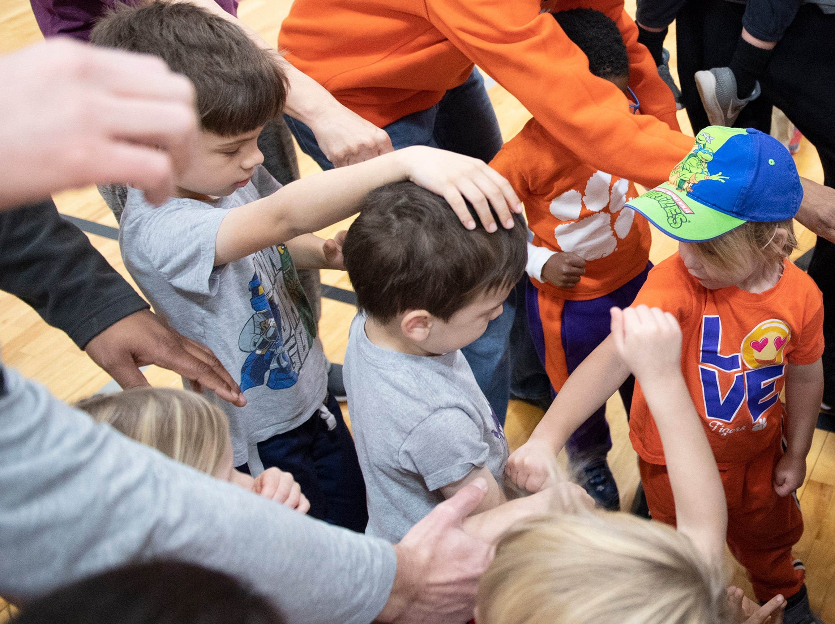 Parents, kids, put their hands together alongside players and coaches from D.W. Daniel High School during the Smart Start Basketball program at Central-Clemson Recreational Center Saturday, Feb. 2, 2019.
