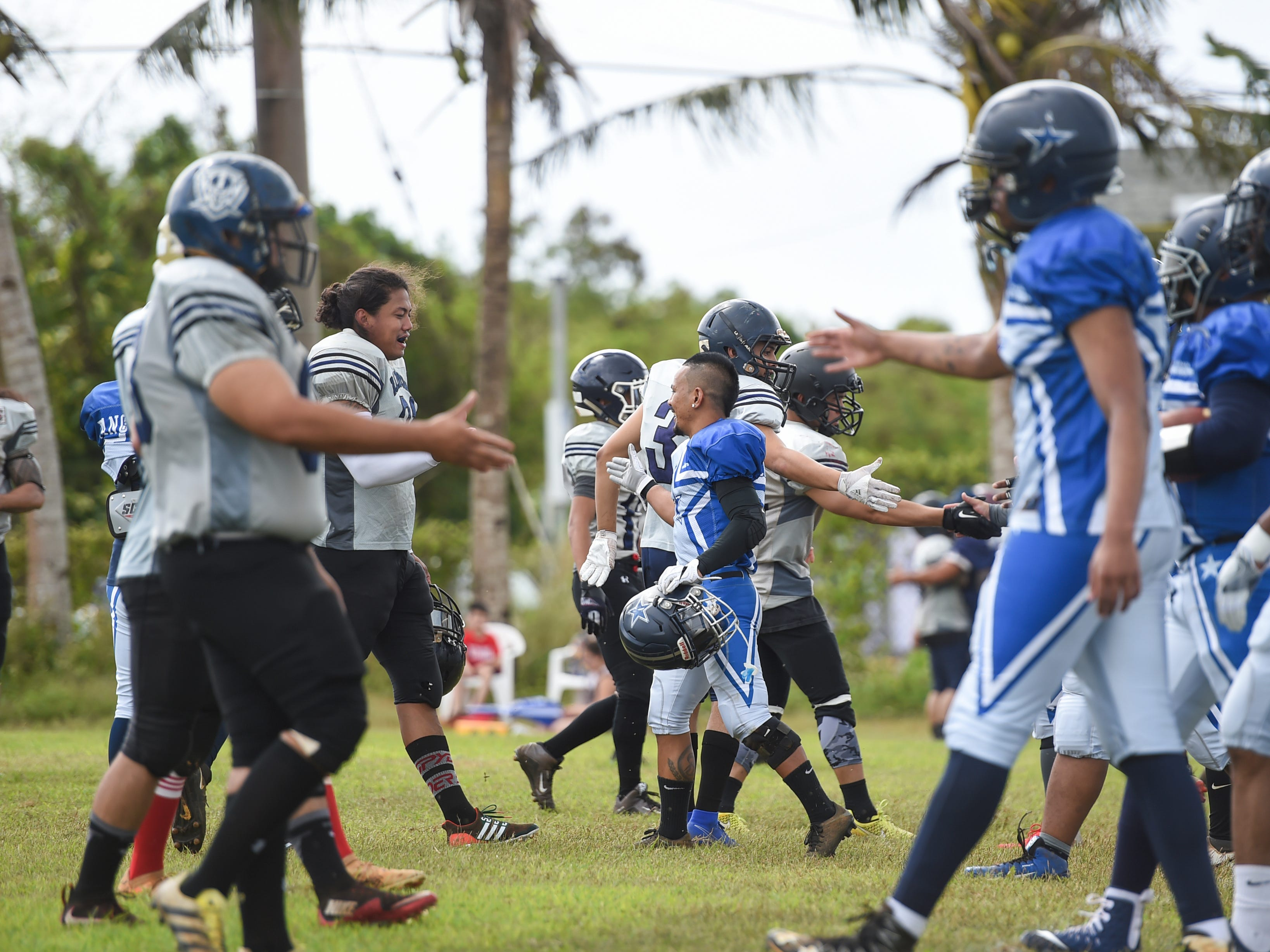 The Guam Raiders and Southern Cowboys display sportsmanship with pregame handshakes during their Budweiser Guahan Varsity Football League game at Eagles Field in Mangilao, Feb. 2, 2019.