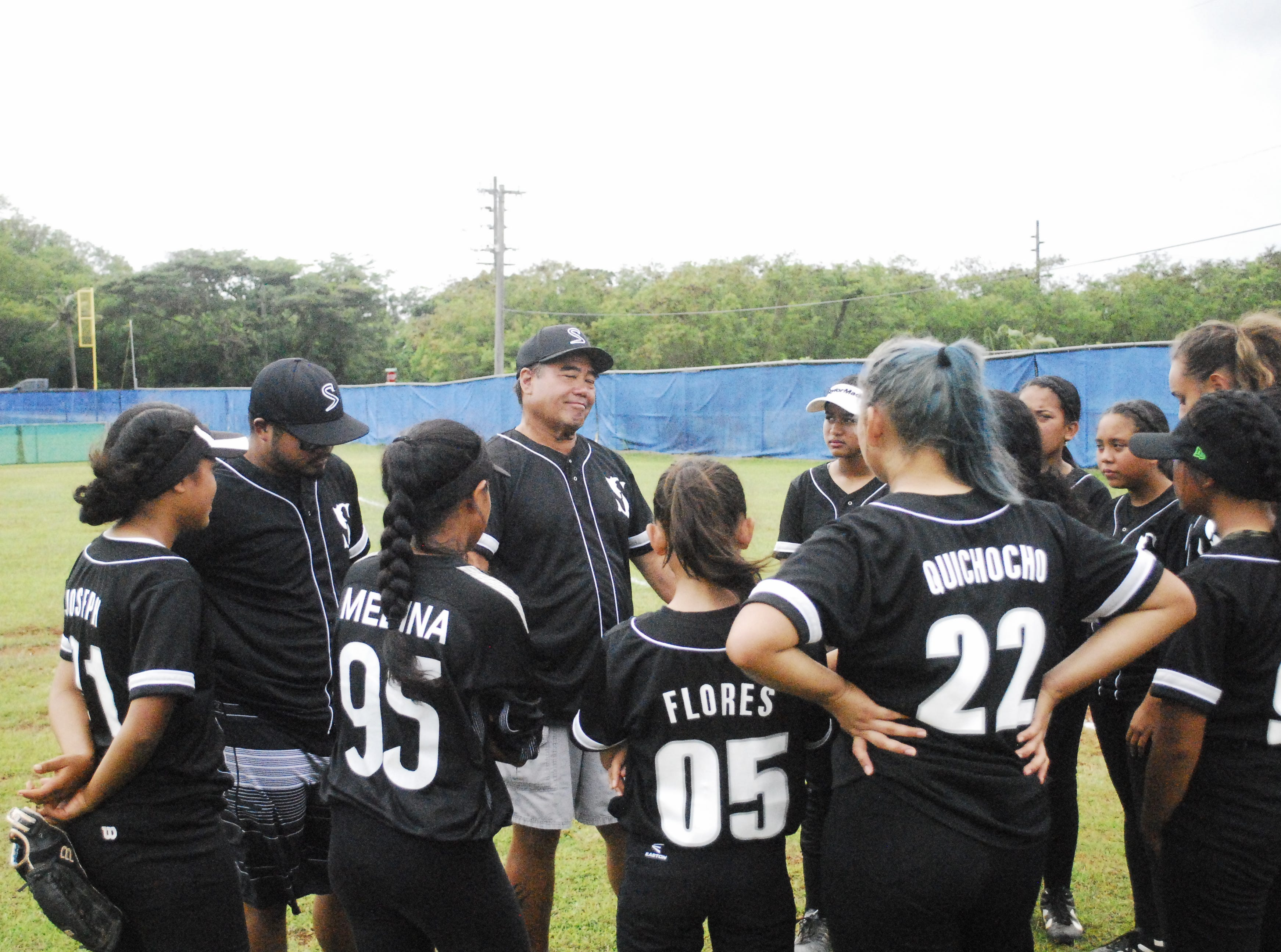 Simon Sanchez Sharks coach Jimmy Naholowaa during his post-game pep talk following the Sharks' 9-8 loss to Academy in a IIAAG High School Girls Softball game on Saturday, Feb. 2 at Tai Field in Mangilao.
