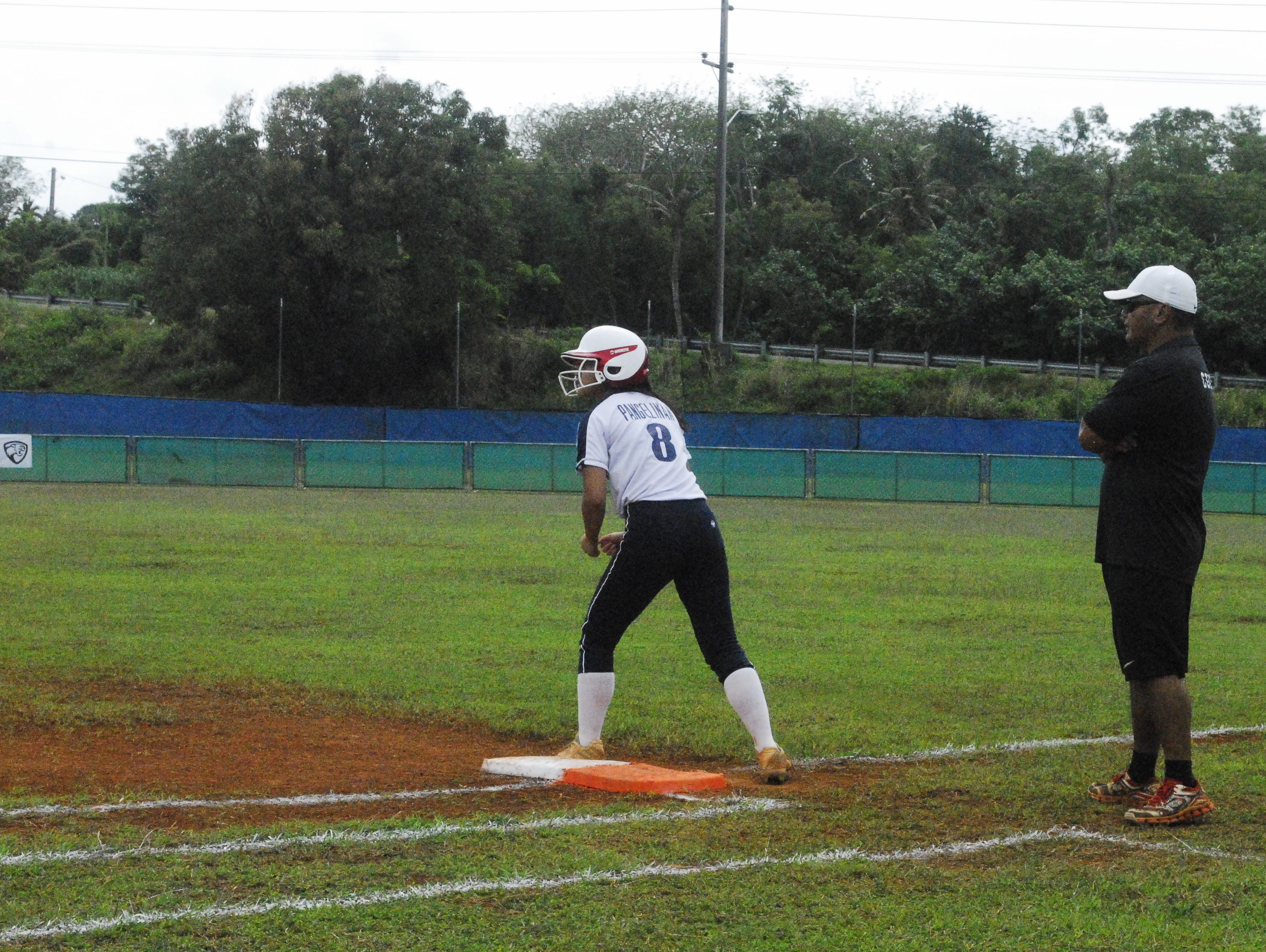 Academy Cougars runner Erin Pangelinan waits for a teammate's hit against Simon Sanchez during their IIAAG High School Girls Softball game on Saturday, Feb. 2 at Tai Field in Mangilao.