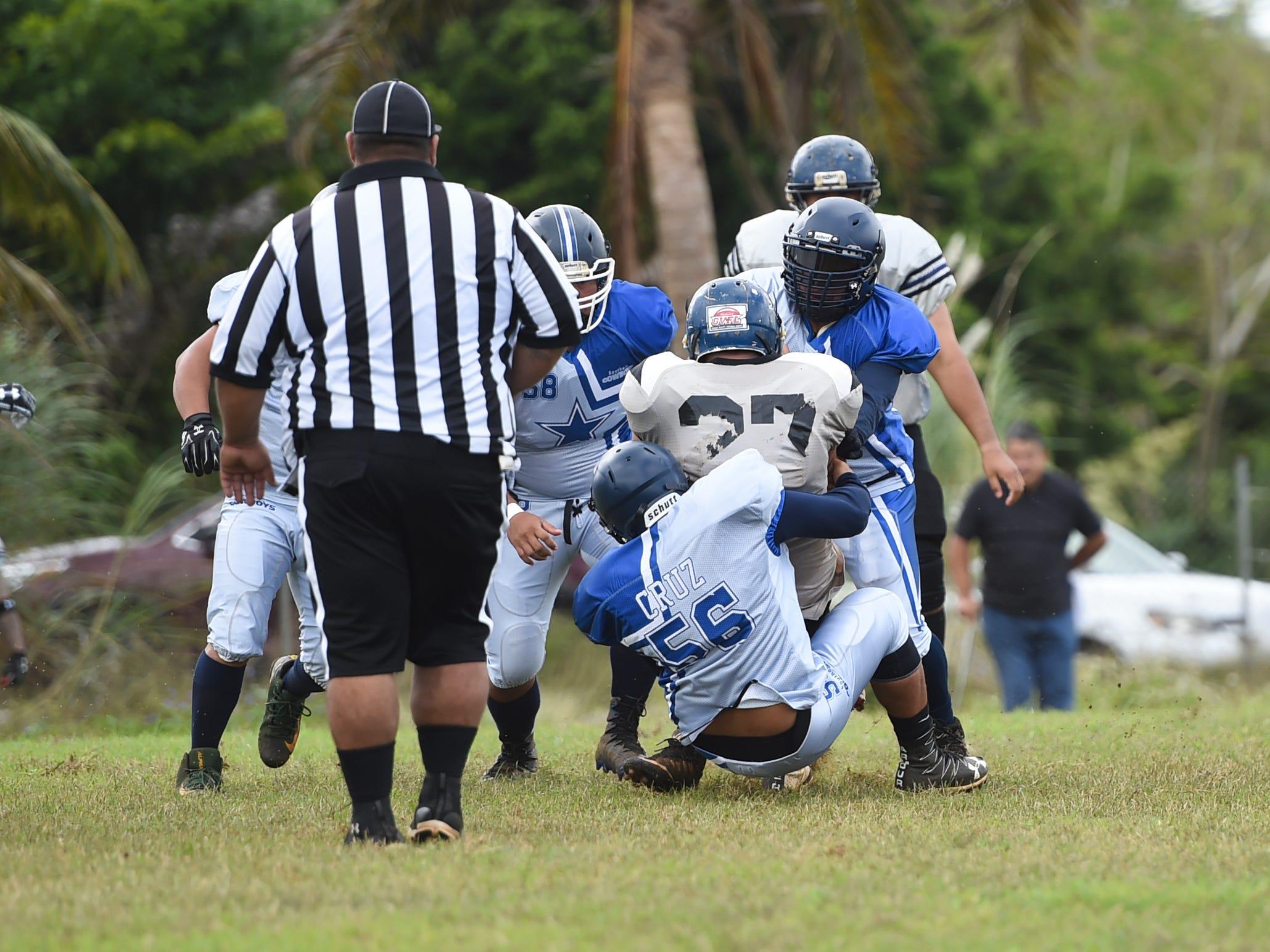 The Cowboys' PJ Cruz (56) gets a tackle against the Guam Raiders during their Budweiser Guahan Varsity Football League game at Eagles Field in Mangilao, Feb. 2, 2019.