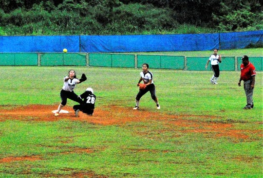 No. 26 Holly Tesei looks for safety at second as Academy shortstop Kaeliah Guerrero waits for the throw during their IIAAG High School Girls Softball game on Saturday, Feb. 2 at Tai Field in Mangilao.