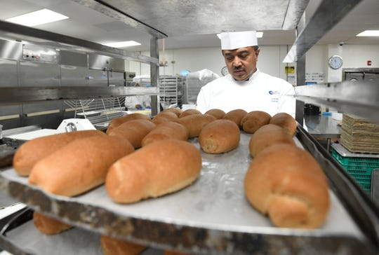 Chef Suharto Suharto, LSG Sky Chefs' executive pastry chef, checks on racks of baked goods, prepared at the company's bakery section in Harmon, on Thursday, Jan. 31, 2019.