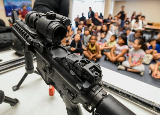"Guam Police Department SWAT officers interact with children and their parents during a Guam Public Library System's ""Saturday Story Hour"" presentation at the Nieves M. Flores Memorial Library in Hagåtña on Saturday, Feb. 2, 2019."