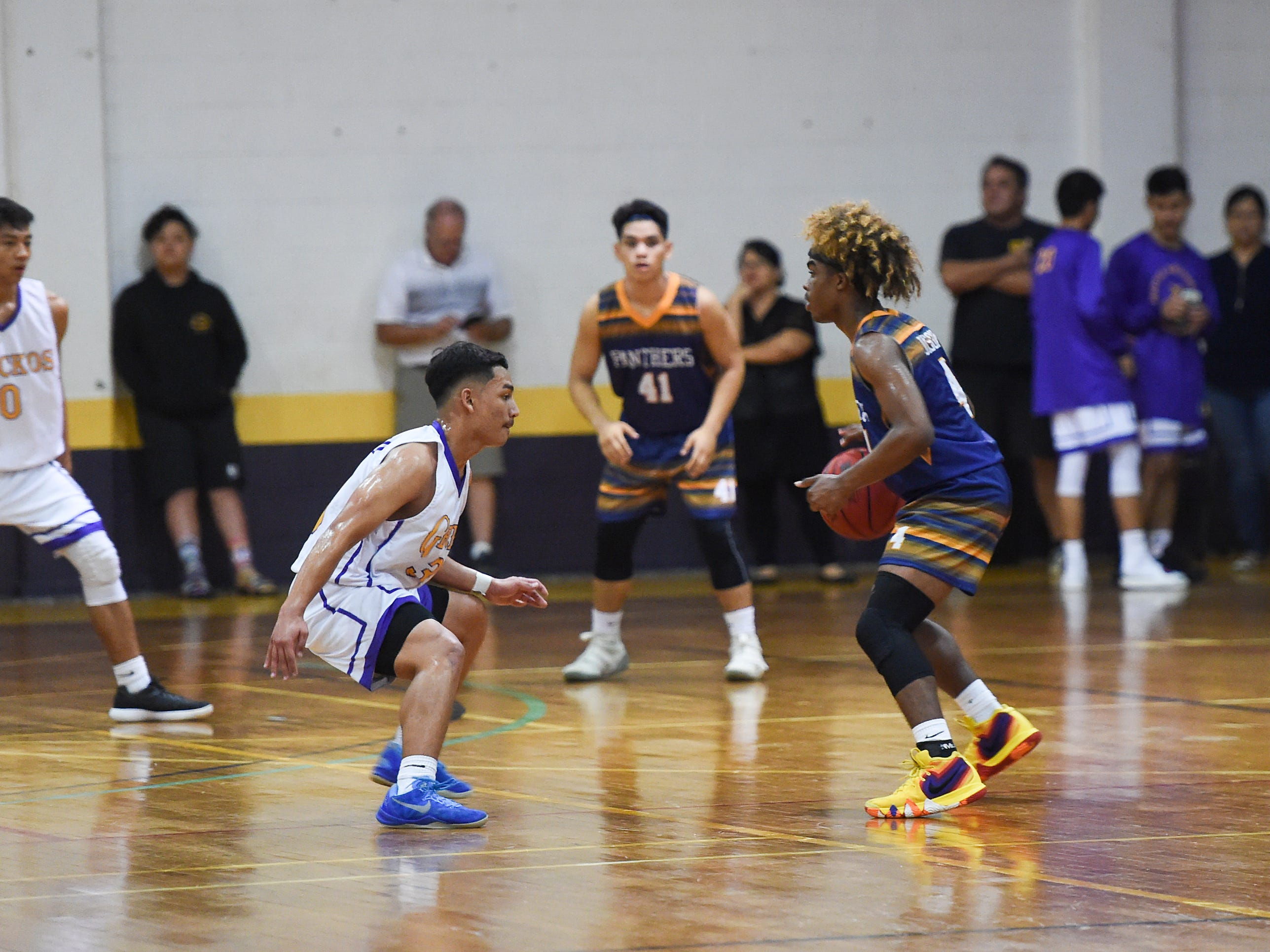 Guam High's Jayson Jackson (4) handles the ball against George Washington player Dylan Trusso during their Independent Interscholastic Athletic Association of Guam Boys' Basketball game at the GW High School gym on Feb. 2, 2019.