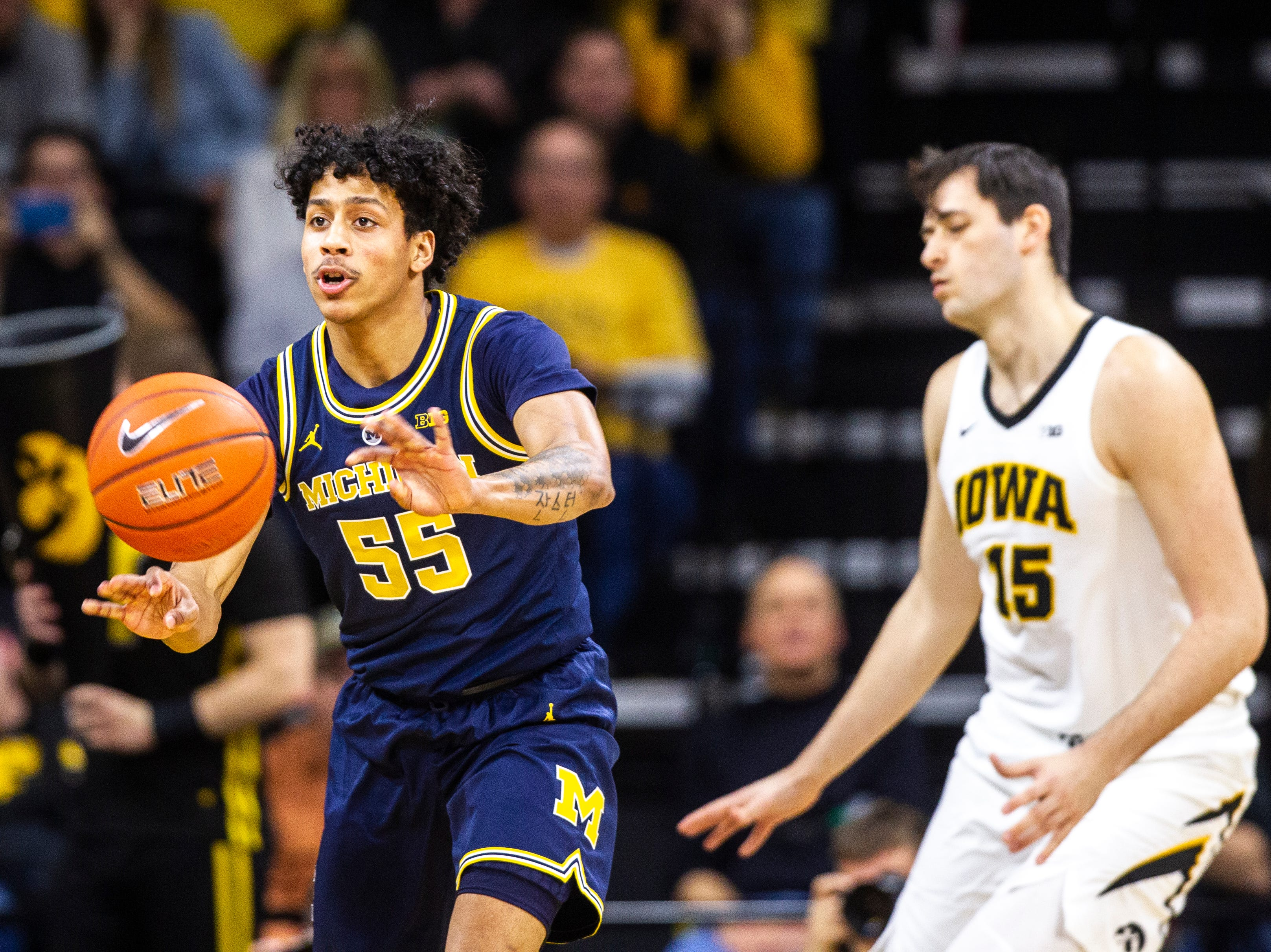 Michigan guard Eli Brooks (55) passes while Iowa forward Ryan Kriener (15) defends during a NCAA Big Ten Conference men's basketball game on Friday, Feb. 1, 2019, at Carver-Hawkeye Arena in Iowa City, Iowa.