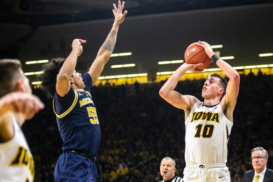 Iowa guard Joe Wieskamp (10) shoots a 3-point basket while Michigan guard Eli Brooks (55) defends during a NCAA Big Ten Conference men's basketball game on Friday, Feb. 1, 2019, at Carver-Hawkeye Arena in Iowa City, Iowa.