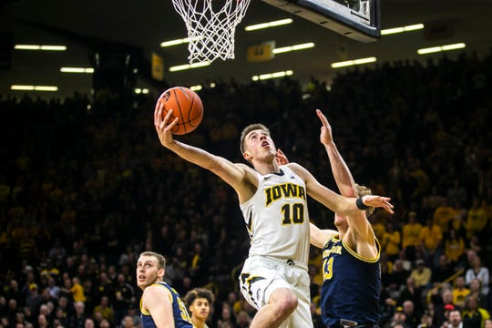 Iowa guard Joe Wieskamp (10) makes a layup past Michigan forward Ignas Brazdeikis (13) during a NCAA Big Ten Conference men's basketball game on Friday, Feb. 1, 2019, at Carver-Hawkeye Arena in Iowa City, Iowa.