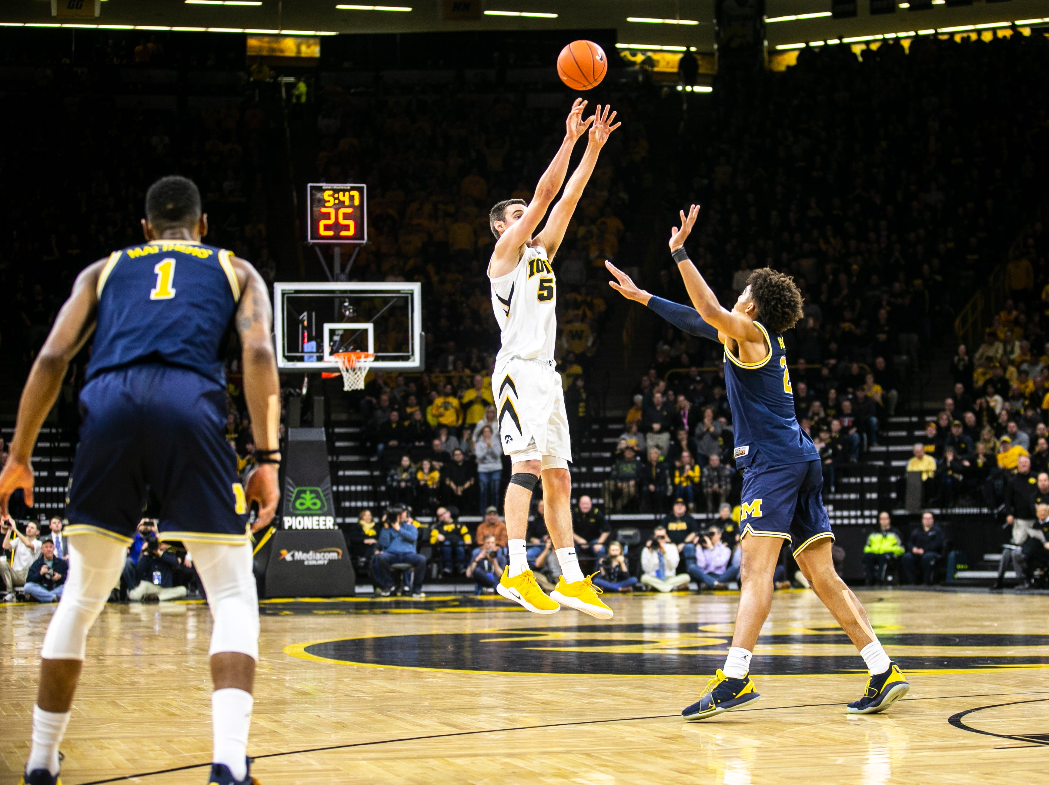 Iowa forward Nicholas Baer (51) shoots a 3-point basket while Michigan guard Jordan Poole (2) defends during a NCAA Big Ten Conference men's basketball game on Friday, Feb. 1, 2019, at Carver-Hawkeye Arena in Iowa City, Iowa.