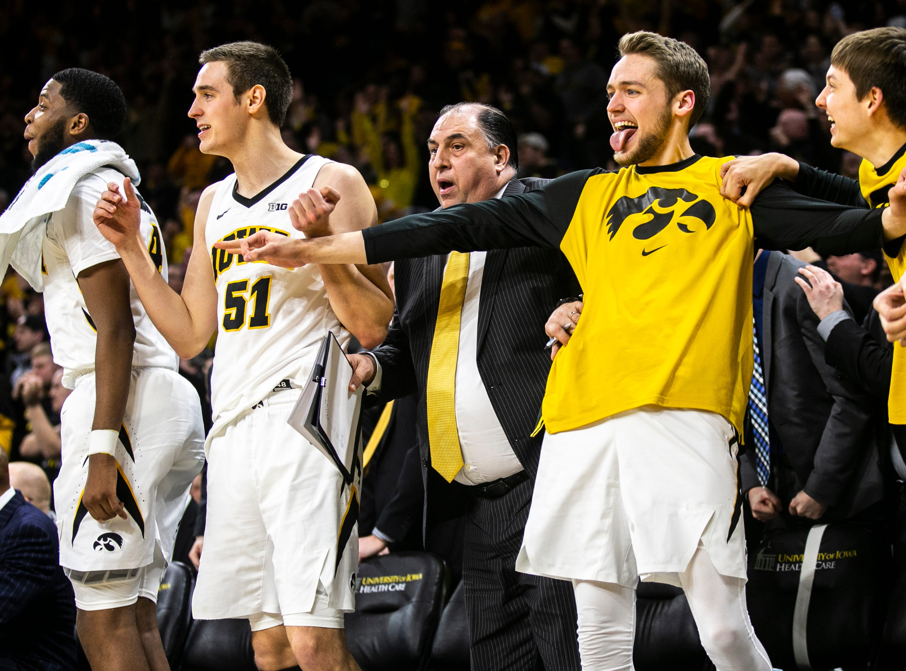 Iowa forward Riley Till celebrates with teammates Isaiah Moss, far left, Nicholas Baer, and Austin Ash, far right,on the bench during a NCAA Big Ten Conference men's basketball game on Friday, Feb. 1, 2019, at Carver-Hawkeye Arena in Iowa City, Iowa.