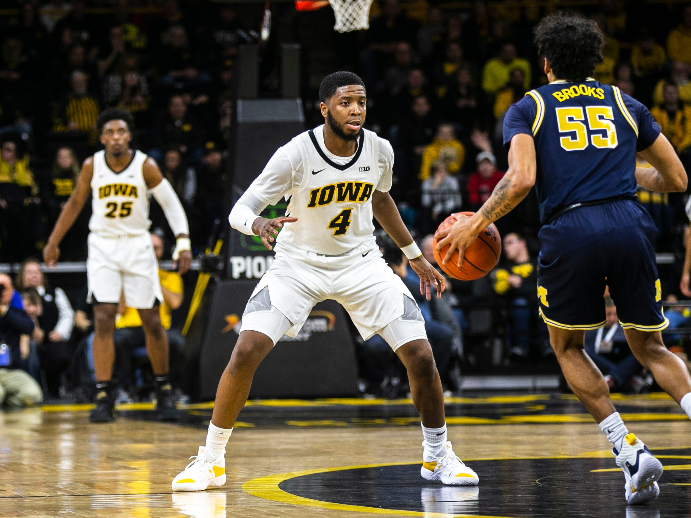 Iowa guard Isaiah Moss (4) defends Michigan guard Eli Brooks (55) during a NCAA Big Ten Conference men's basketball game on Friday, Feb. 1, 2019, at Carver-Hawkeye Arena in Iowa City, Iowa.