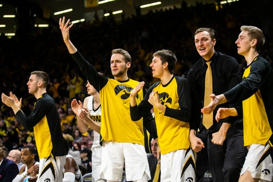 Iowa sophomore forward Jack Nunge, wearing a black shirt and gold tie, celebrates with teammates during the Hawkeyes' upset of Michigan on Feb. 1. Nunge is redshirting this season, but still engaged with the team and eagerly anticipating what extra size will mean for him in his final three years.