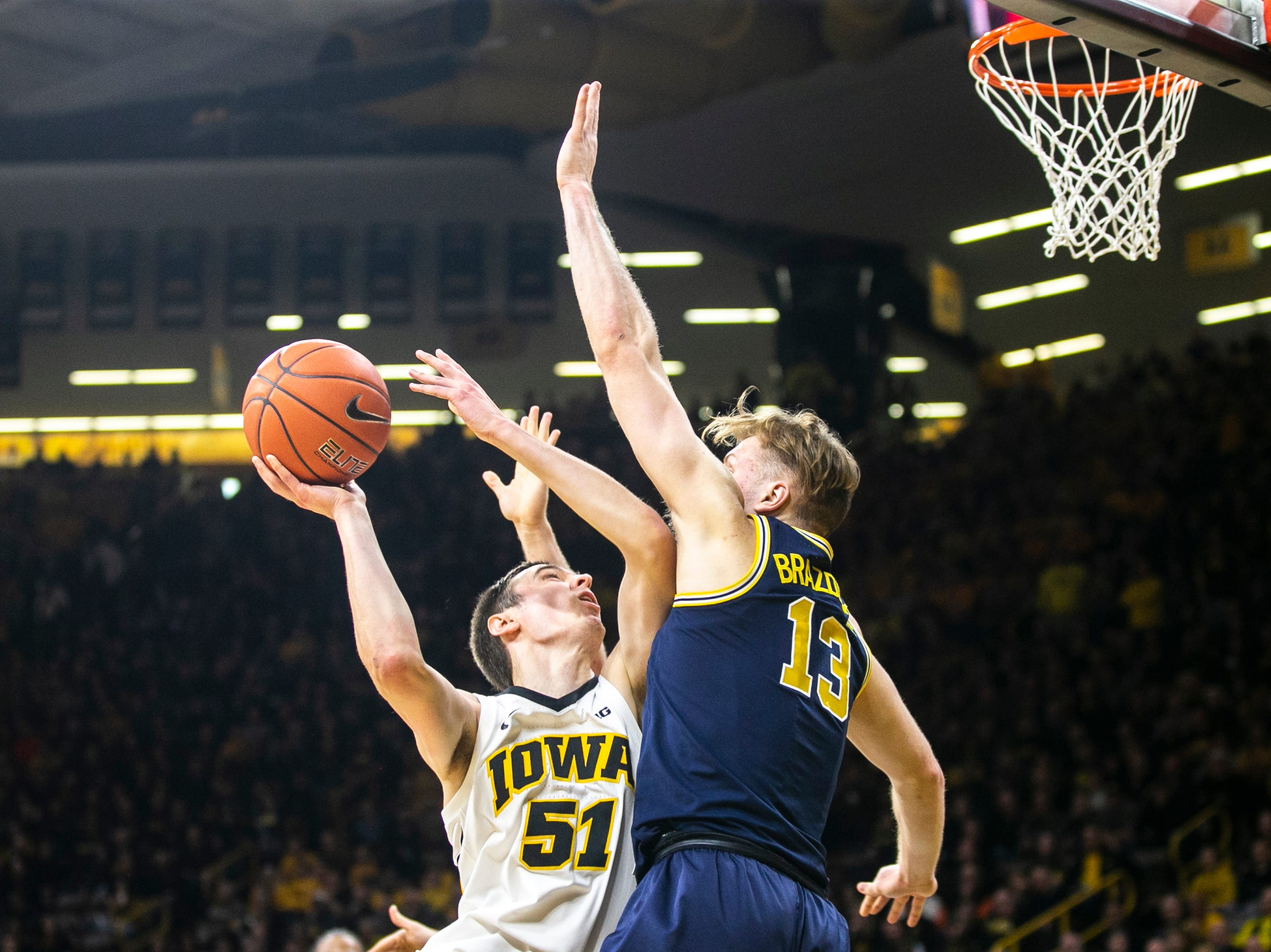 Iowa forward Nicholas Baer (51) gets fouled by Michigan forward Ignas Brazdeikis (13) during a NCAA Big Ten Conference men's basketball game on Friday, Feb. 1, 2019, at Carver-Hawkeye Arena in Iowa City, Iowa.