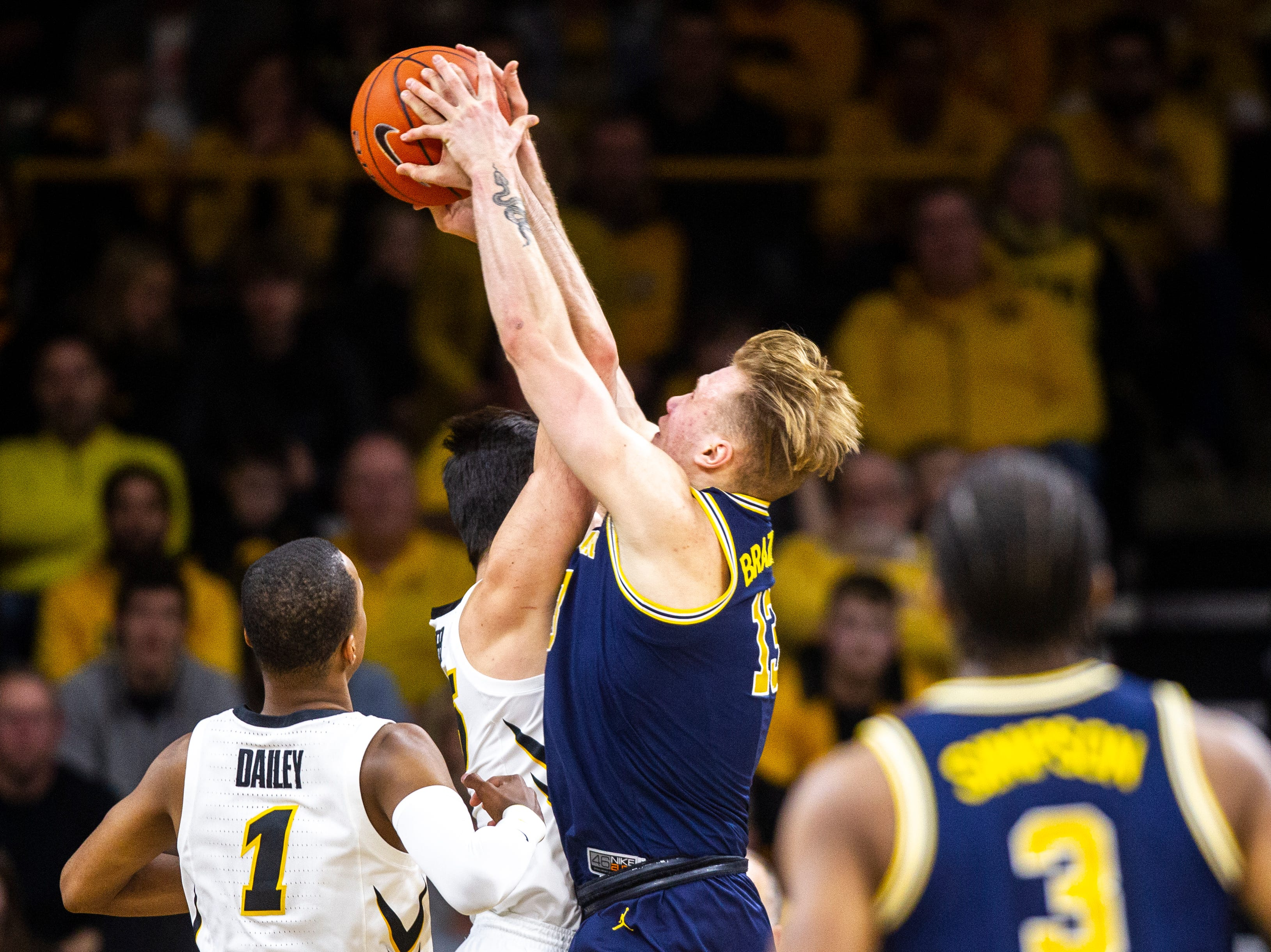 Michigan forward Ignas Brazdeikis (13) fouls Iowa forward Ryan Kriener while going for a rebound during a NCAA Big Ten Conference men's basketball game on Friday, Feb. 1, 2019, at Carver-Hawkeye Arena in Iowa City, Iowa.