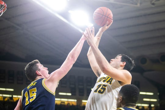 Iowa forward Ryan Kriener, right, shoots while being defended by Michigan center Jon Teskeduring a NCAA Big Ten Conference men's basketball game on Friday, Feb. 1, 2019, at Carver-Hawkeye Arena in Iowa City, Iowa.