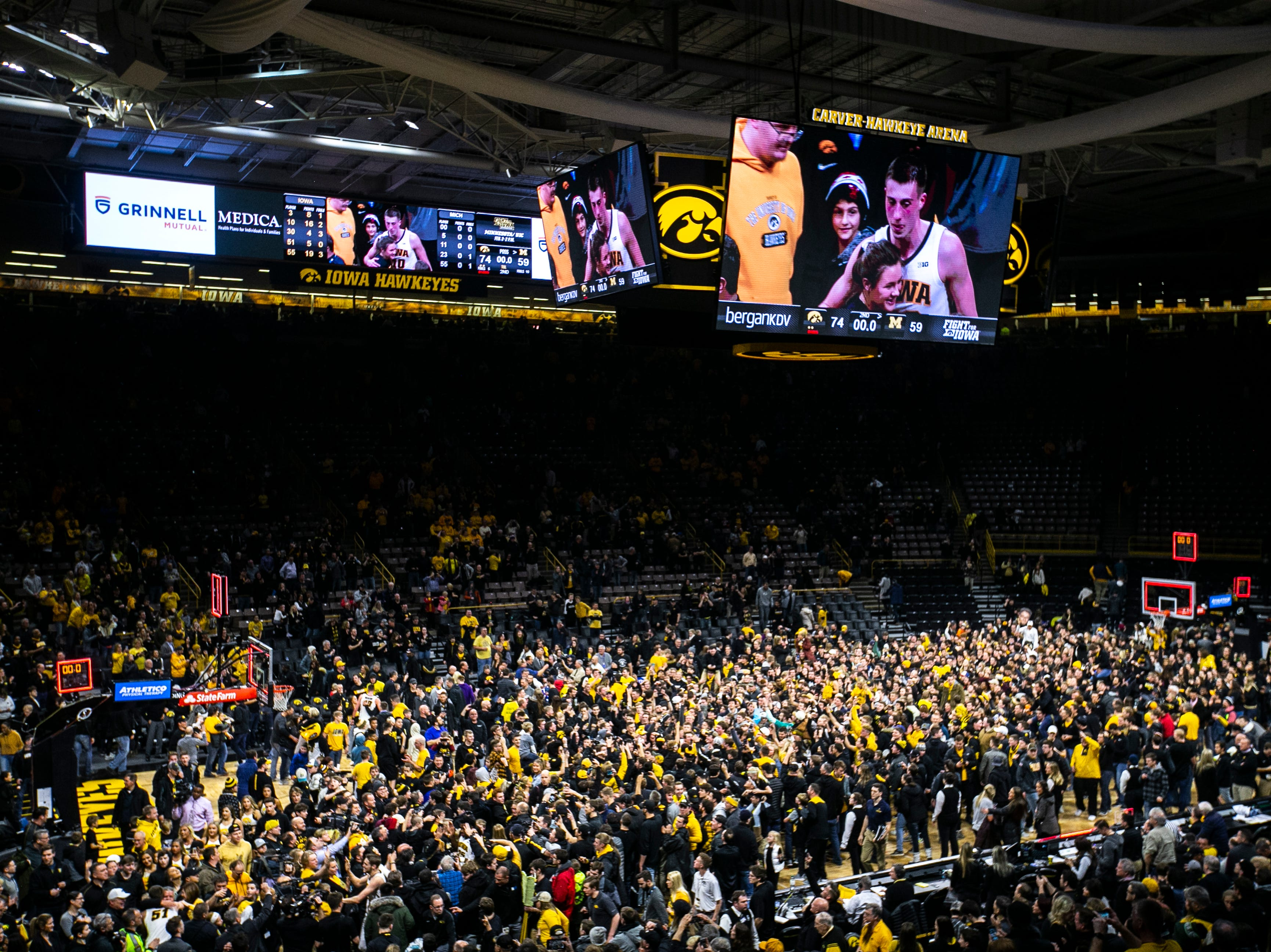 Iowa fans rush the court after a NCAA Big Ten Conference men's basketball game on Friday, Feb. 1, 2019, at Carver-Hawkeye Arena in Iowa City, Iowa. The Hawkeyes defeated Michigan's Wolverines, 74-59.