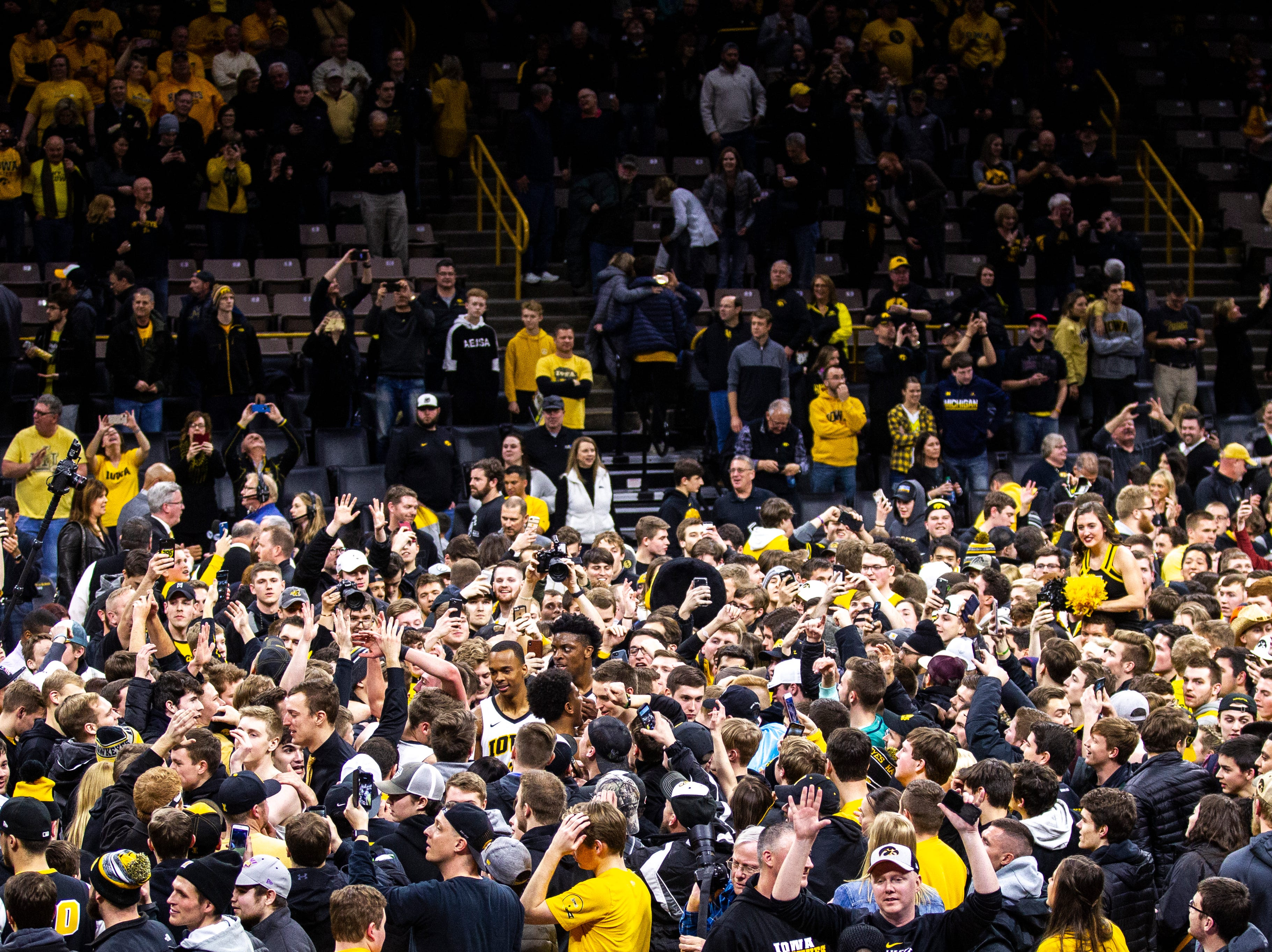 Iowa fans celebrate while Hawkeyes basketball players (from bottom left diagonally) Cordell Pemsl, Michael Baer, Jack Nunge, Maishe Dailey and Tyler Cook make their way off the court during a NCAA Big Ten Conference men's basketball game on Friday, Feb. 1, 2019, at Carver-Hawkeye Arena in Iowa City, Iowa. The Hawkeyes defeated Michigan's Wolverines, 74-59.
