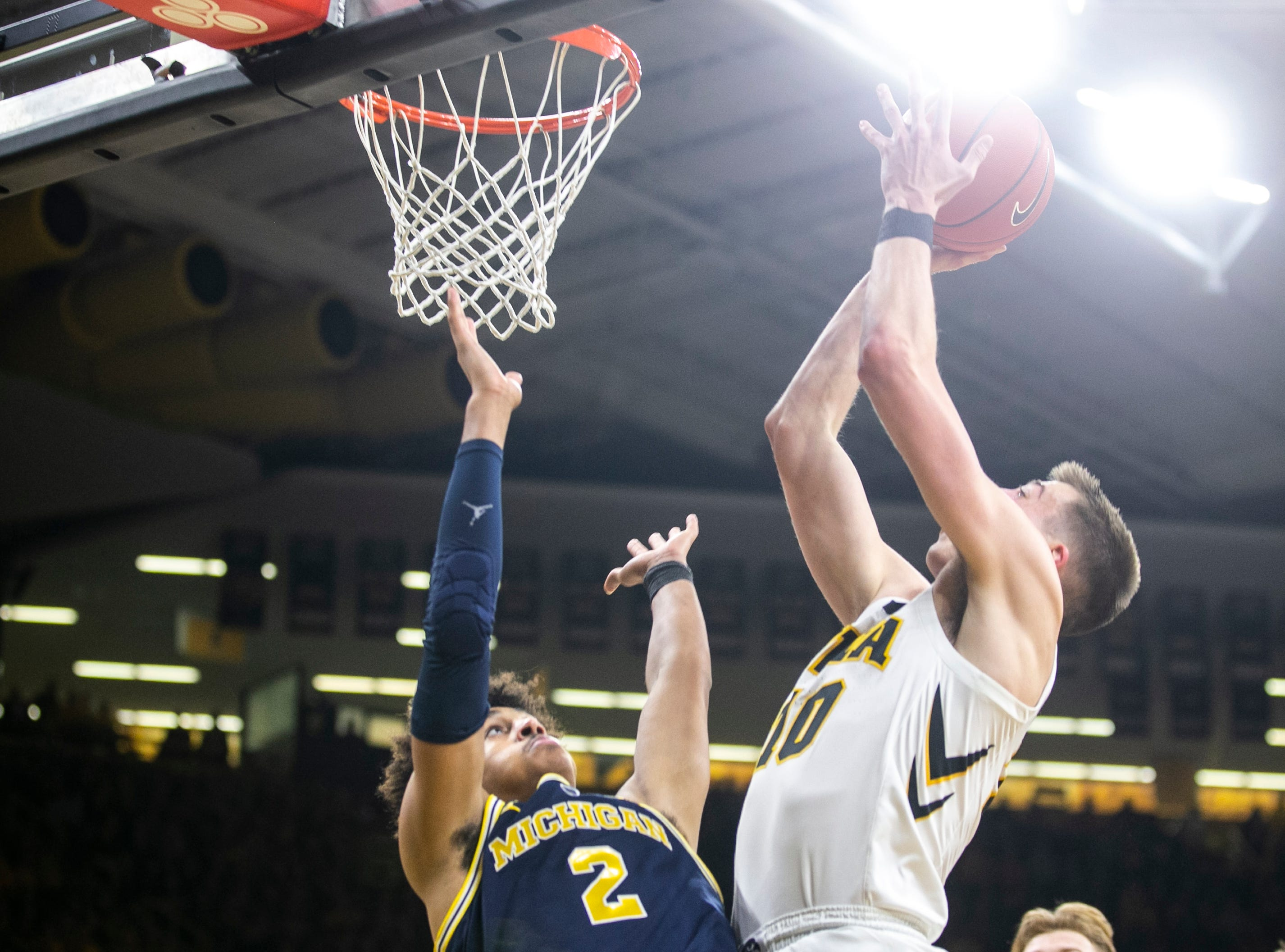 Iowa guard Joe Wieskamp (10) makes a layup while Michigan guard Jordan Poole (2) defends during a NCAA Big Ten Conference men's basketball game on Friday, Feb. 1, 2019, at Carver-Hawkeye Arena in Iowa City, Iowa.