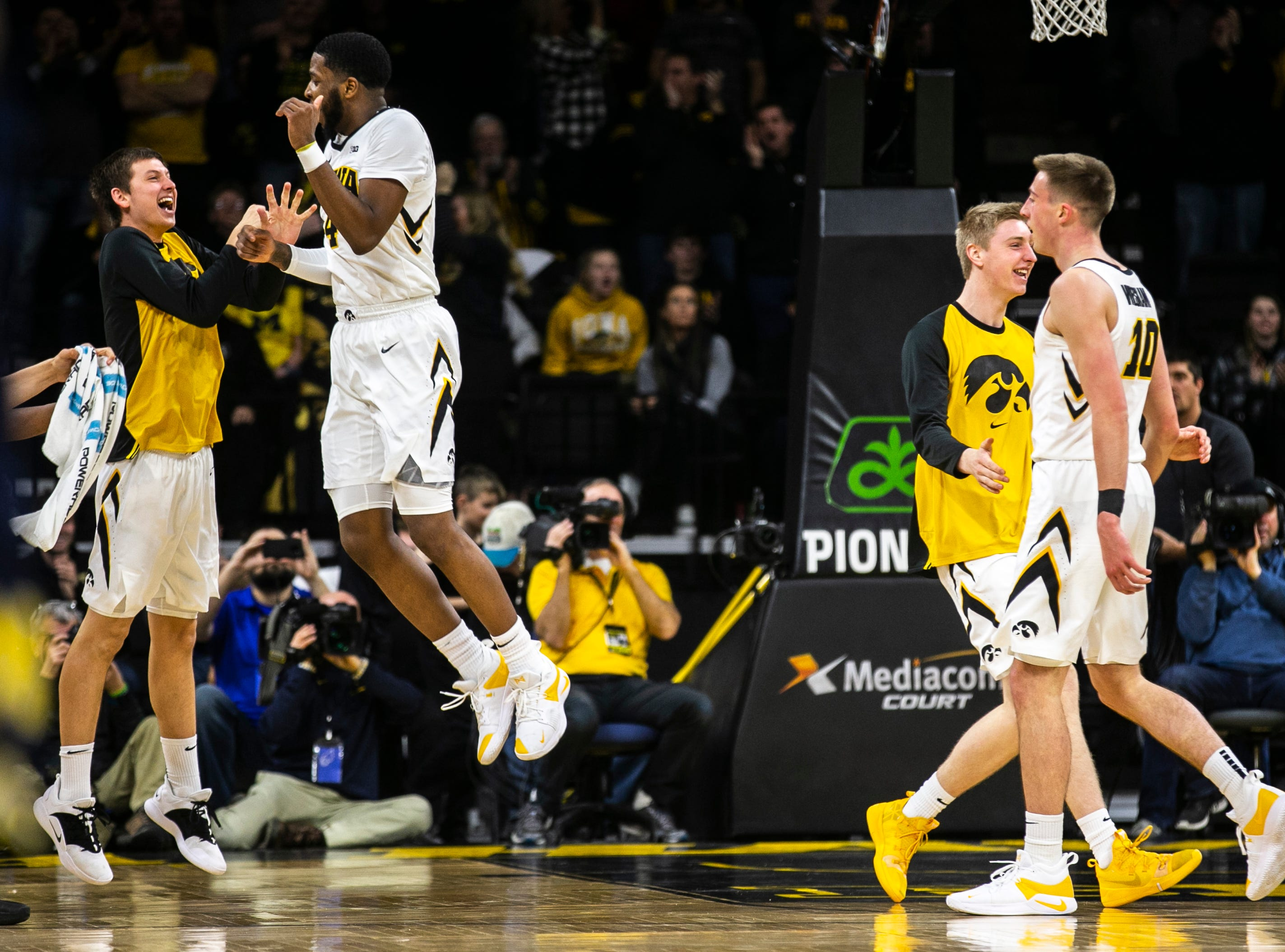 Iowa guard Isaiah Moss (4) celebrates while Austin Ash, far left, while Iowa guard Joe Wieskamp (10) gets a high-five from Michael Baer heading into a timeout during a NCAA Big Ten Conference men's basketball game on Friday, Feb. 1, 2019, at Carver-Hawkeye Arena in Iowa City, Iowa.