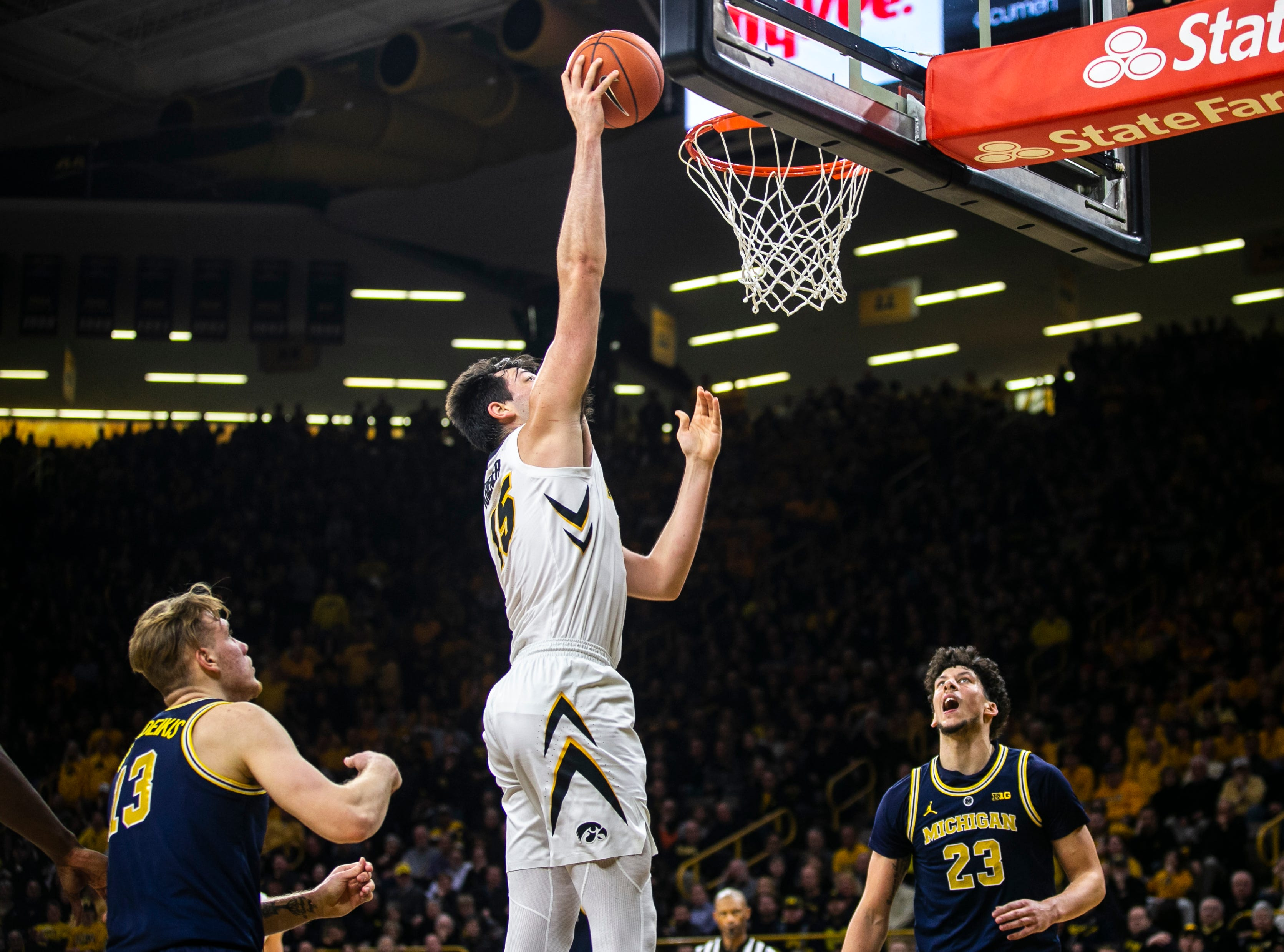 Iowa forward Ryan Kriener (15) makes a basket while Michigan forwards Ignas Brazdeikis (13) and Brandon Johns Jr. look on during a NCAA Big Ten Conference men's basketball game on Friday, Feb. 1, 2019, at Carver-Hawkeye Arena in Iowa City, Iowa.