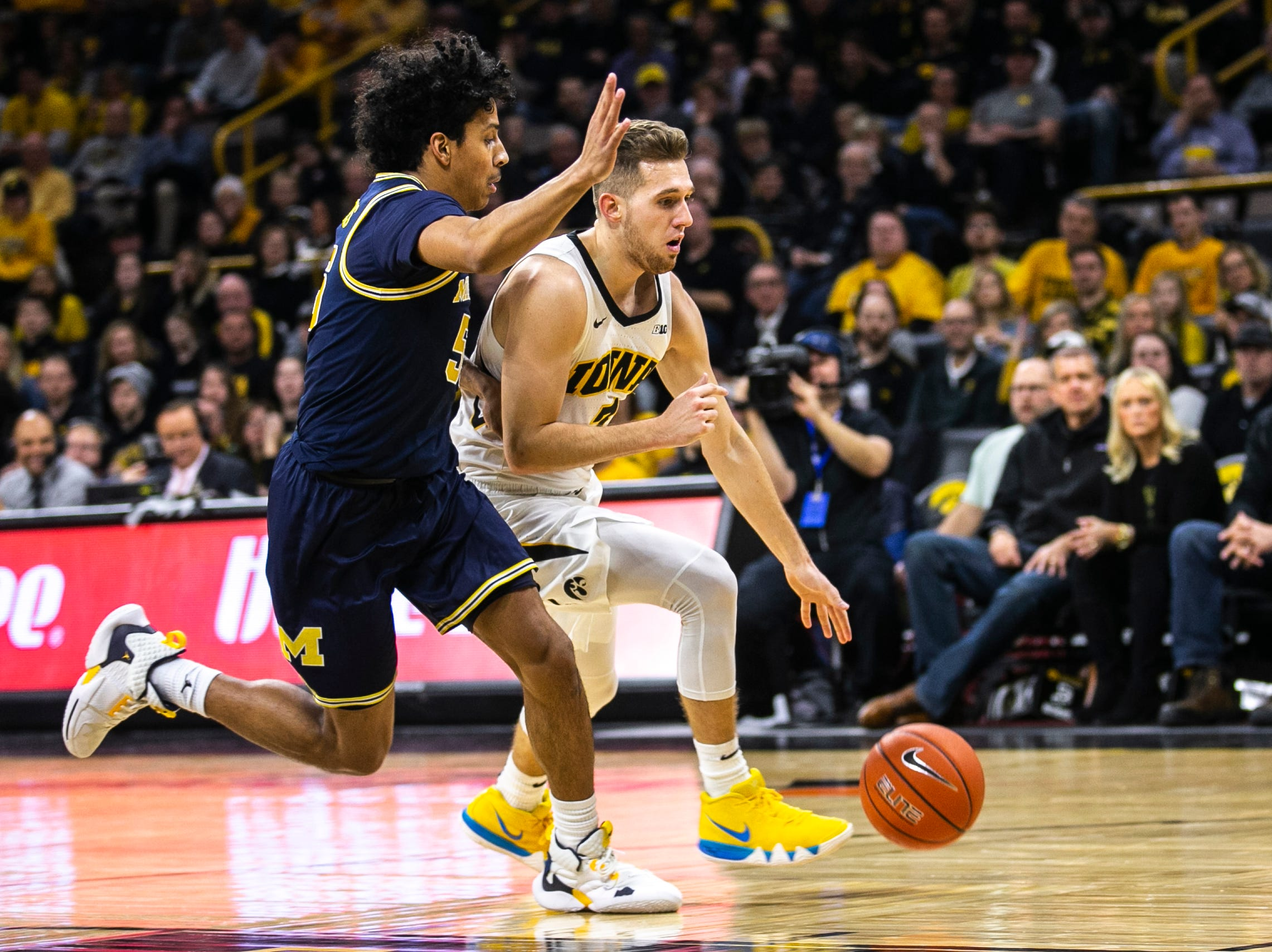 Iowa guard Jordan Bohannon (3) drives to the basket while Michigan guard Eli Brooks (55) defends during a NCAA Big Ten Conference men's basketball game on Friday, Feb. 1, 2019, at Carver-Hawkeye Arena in Iowa City, Iowa.