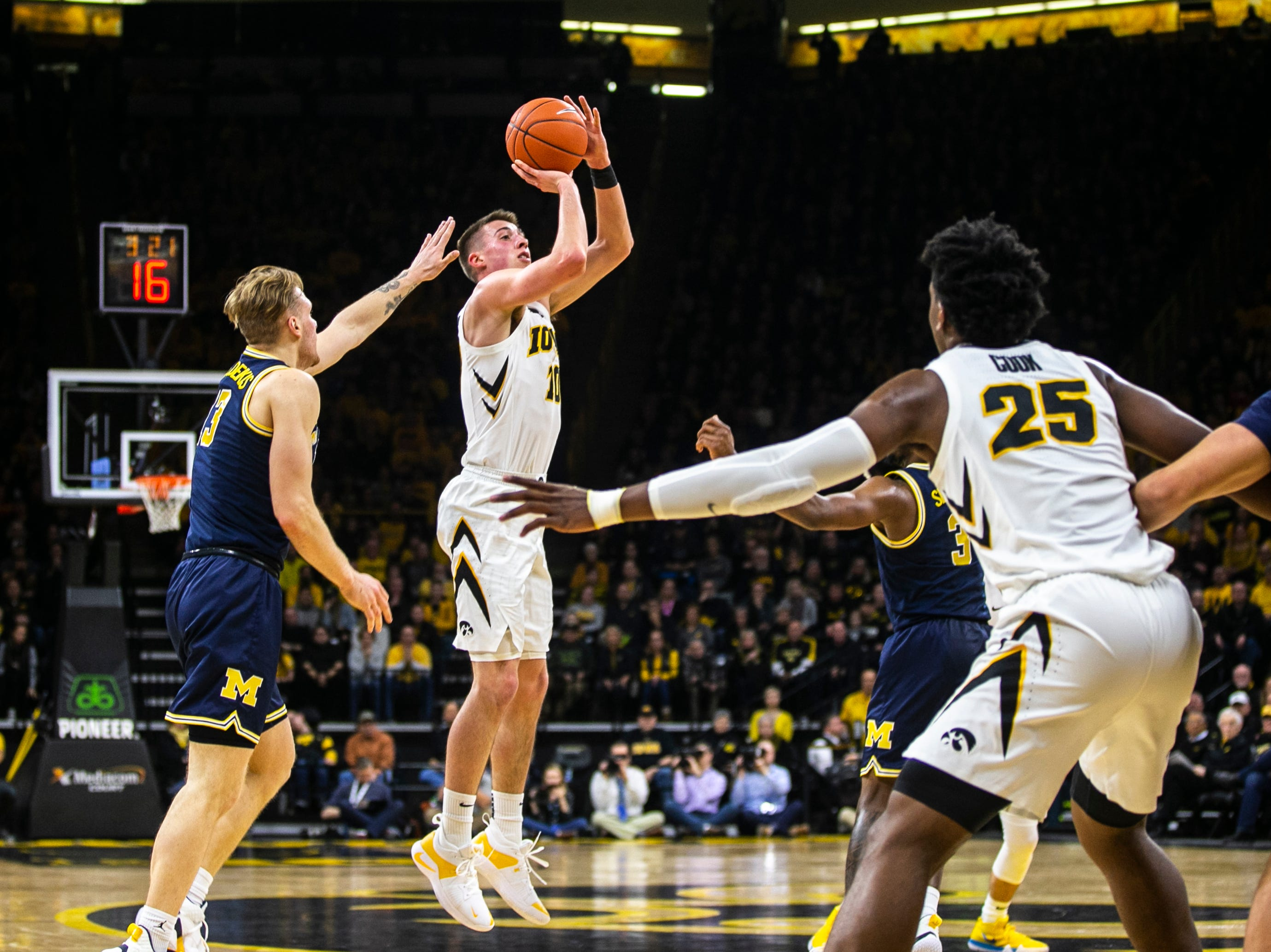 Iowa guard Joe Wieskamp (10) shoots a 3-point basket while Michigan forward Ignas Brazdeikis (13) during a NCAA Big Ten Conference men's basketball game on Friday, Feb. 1, 2019, at Carver-Hawkeye Arena in Iowa City, Iowa.